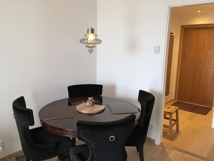 Dining-table adjacent to living room are and kitchen with entrance in the background
