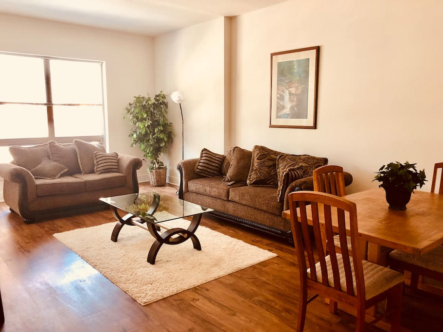 Large, sunlit living and dining area. Dining table seats four. Comfy sofa and loveseat.