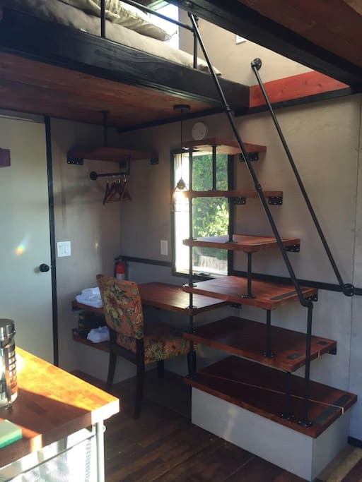 Contemporary open concept rethinks tiny house experience to be more open, spacious, and industrial-cozy.  Robert conceived of this unique stair-shelf-storage unit, with built-in writing desk and open closet.