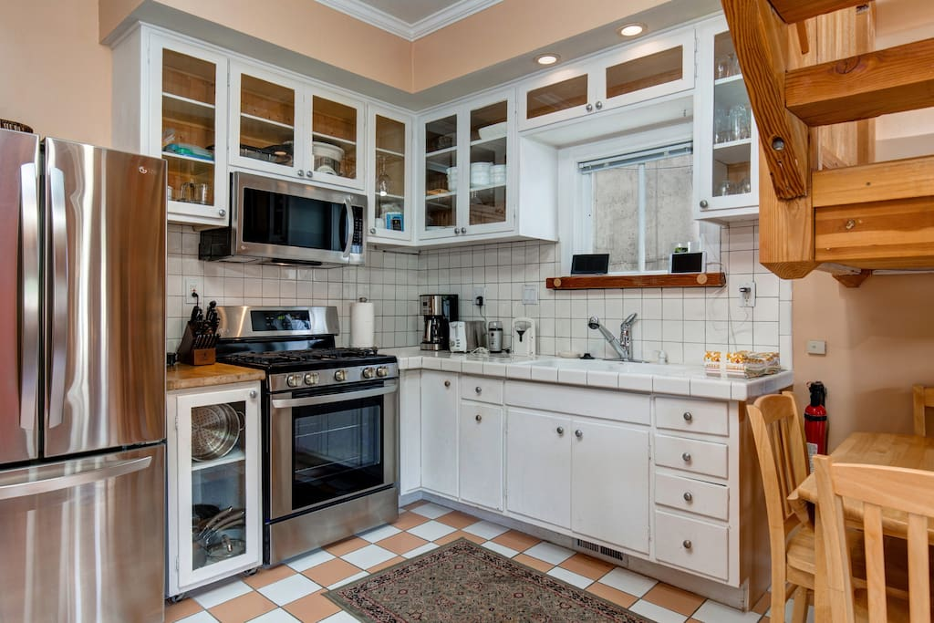 Gas range, subway tile backsplash, glass-front cabinetry