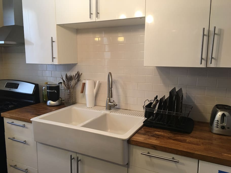 Renovated kitchen with stainless steel appliances, double farm sink, and butcher block counters.