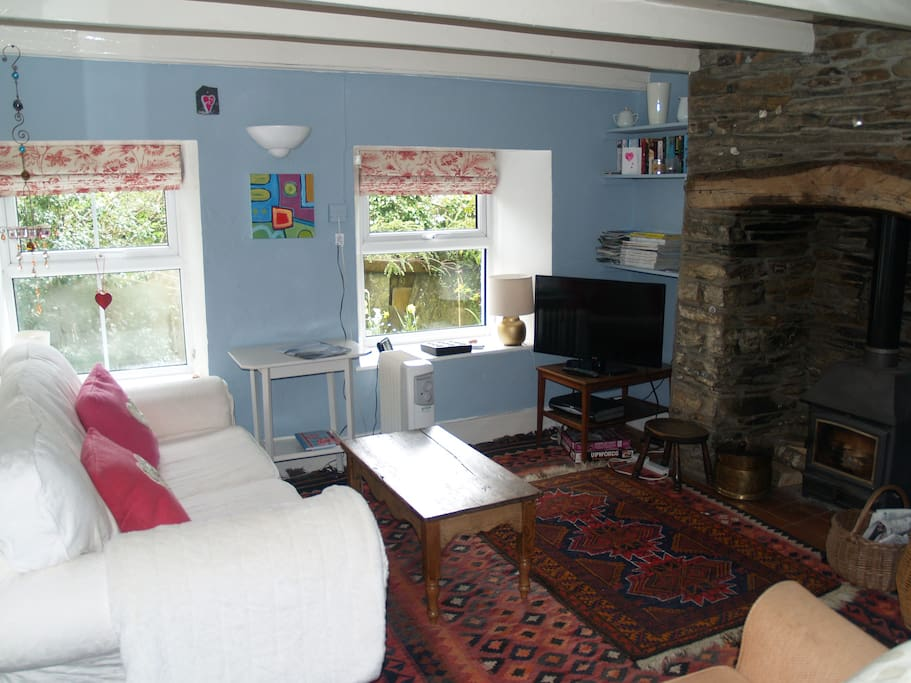 Cosy living room with original art,woodburner, sofa and armchair,tv, books, travel guides.