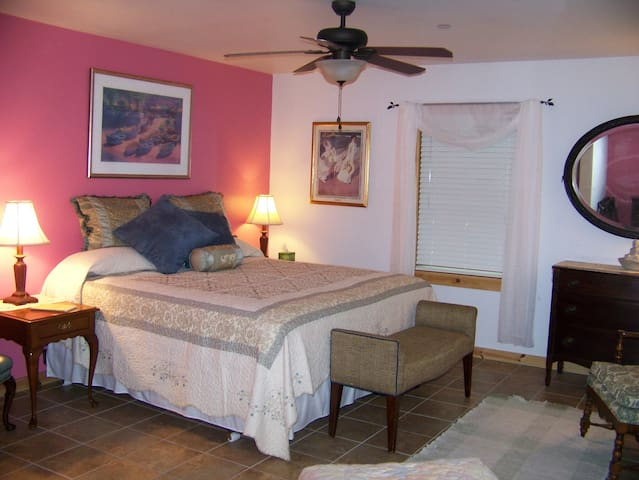 West Bedroom with king size bed, private full bathroom, ceiling fan & climate control.