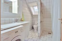 Badeværelse med brusebad og vaskemaskine