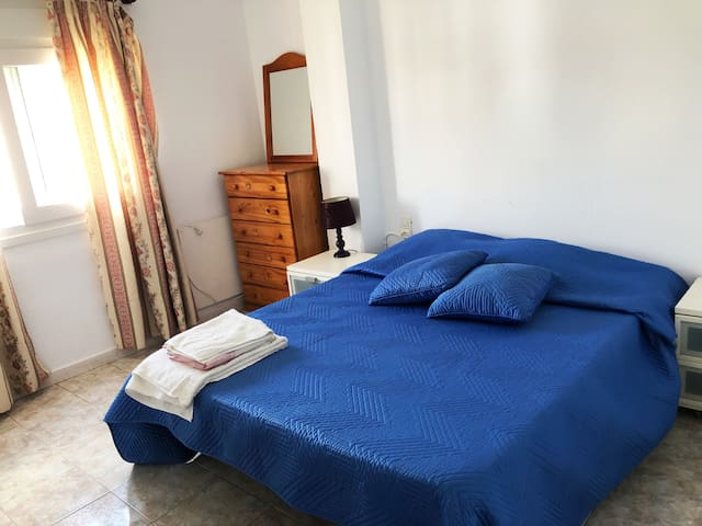 The bedroom which has a double bed, a fantastic view of the mountains and plenty of space for keeping clothes and suitcases.