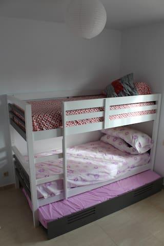 Vue de la 3ème chambre avec deux lits superposés et un lit coulissant