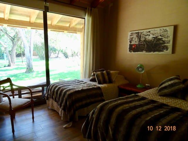 Pieza 1 Dos camas + una cama nido, closet y velador central Cortinas BlackOut y salida al jardín.
