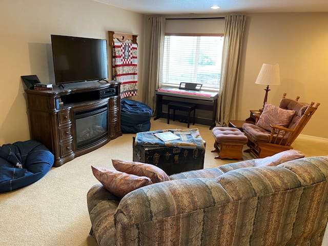 Living room includes queen pullout couch bed, Roku flat screen tv, piano keyboard, and electric fireplace.