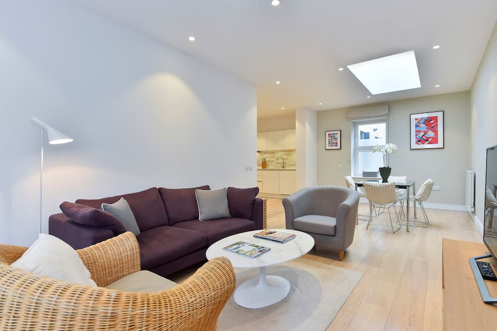 The light, spacious living area boasts a sofa, two armchairs, flat screen TV and a dining table for 4 people.