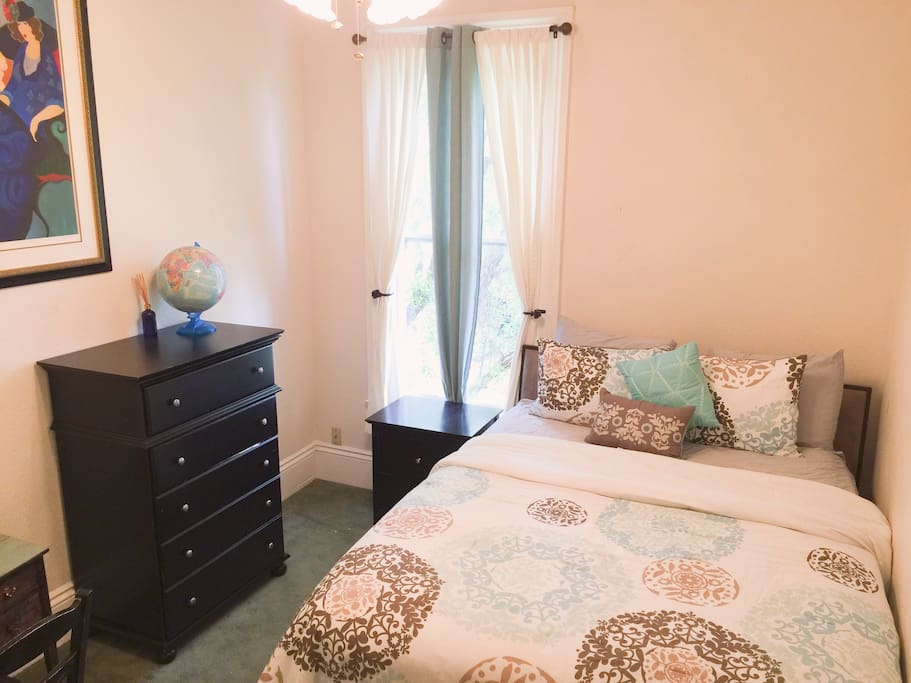 Queen size bed with a desk, dresser, nightstand, and closet with hangers.