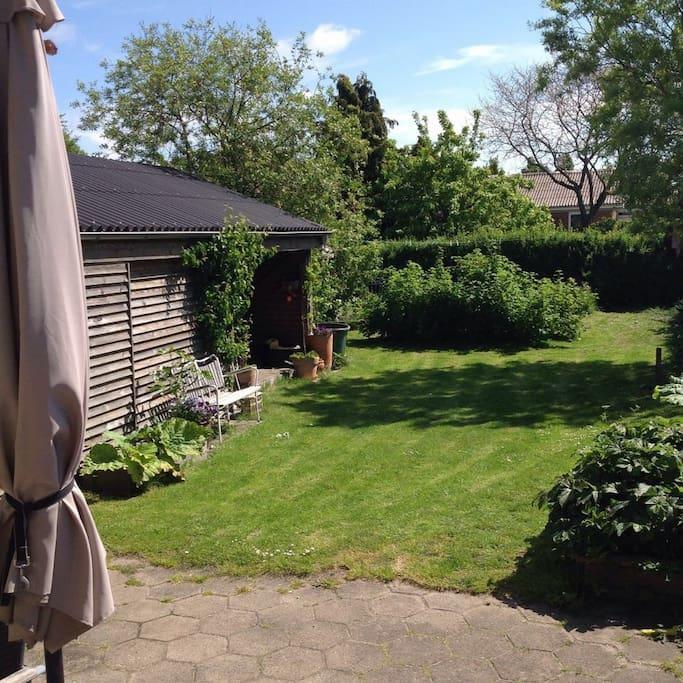 Overdækket rum i haven med seng og ekstra madras, hvis nogen vil sove ude eller blot slappe af i skyggen i løbet at dagen