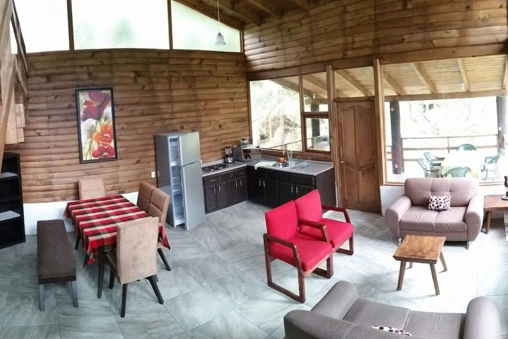 Área abierta con ventanales y chimenea frente a la sala