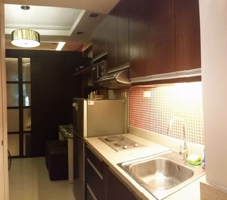 kitchen has utensils, microwave oven, refrigerator and stove
