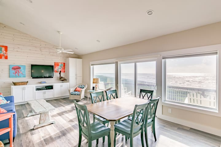 This open-concept living area is anchored by a wall of windows that overlook the beach.