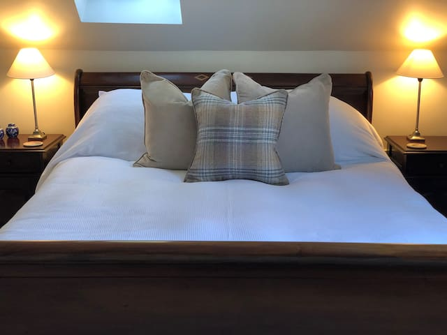 A large, comfortable king-size bed with fresh white linen in a spacious and private room, separate to the main house