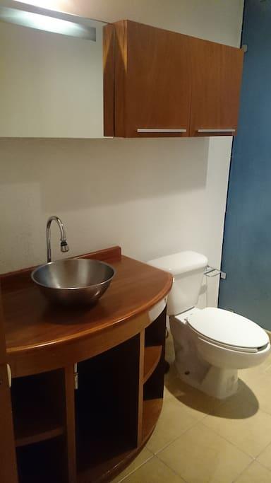 Baño amplio con regadera fija y de mano.