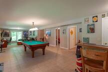 Pool table and dart board with walk-out to backyard.