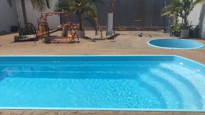 Quarto  com área de lazer com piscinas e churrasqu