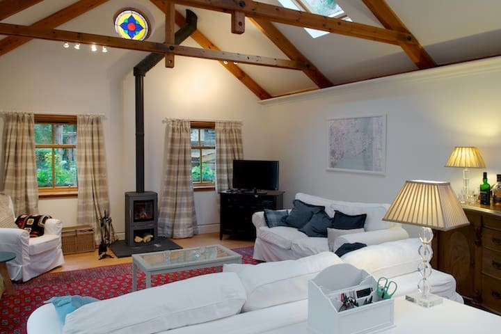 Spacious living area with high ceilings and large windows providing plenty of light