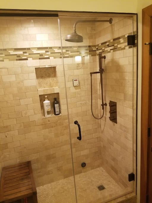 New marble steam bath with rain shower and teak bench
