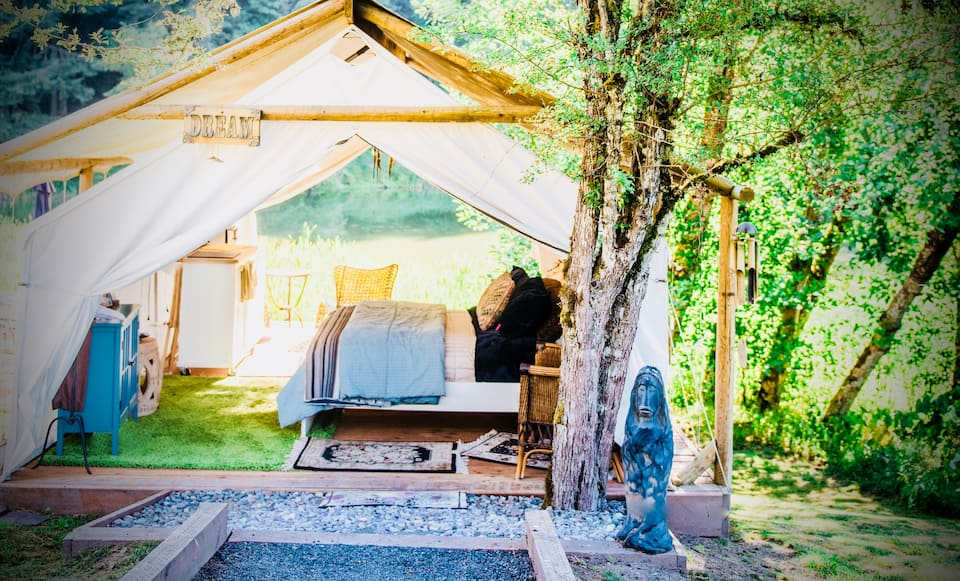 Cozy Glamping Getaway, an AirBnB location featuring outdoor room under wooden structure with white fabric covering.