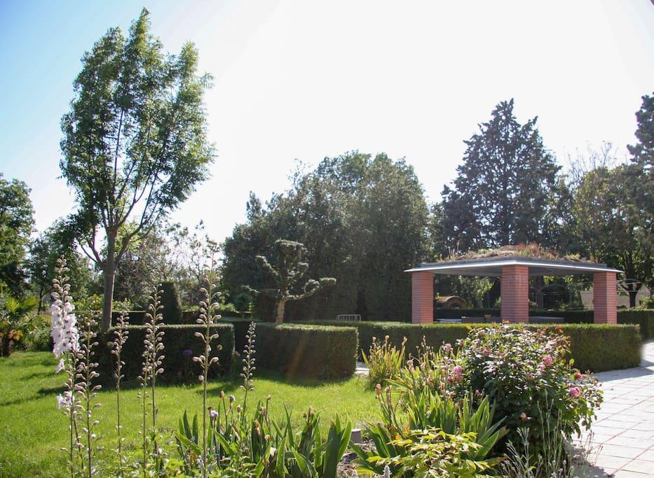 le jardin entouré de buis centenaires accueillant les petits déjeuners en été