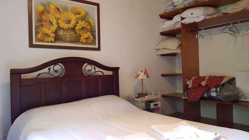 Quarto girassol com 1 cama de casal e 1 cama de solteiro.