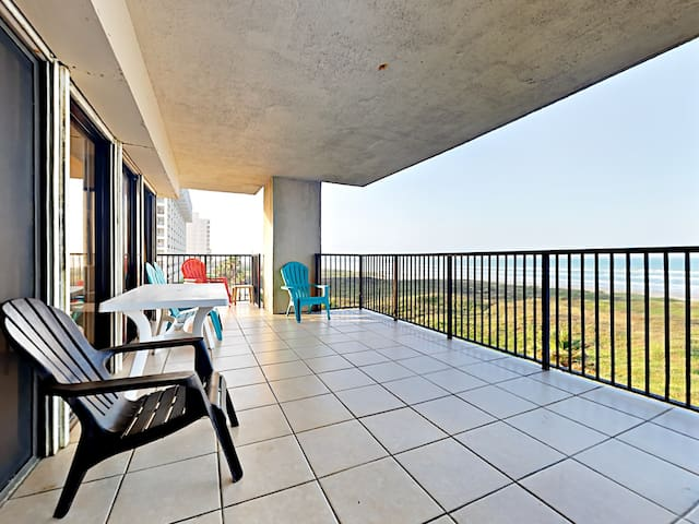 The spacious covered balcony includes 5 Adirondack chairs and a patio table.