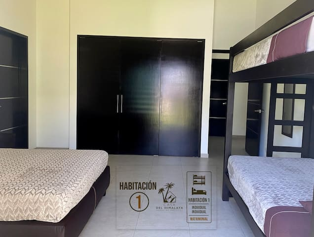 Habitación 1, 2 camas individuales y una matrimonial; con vista al jardín.