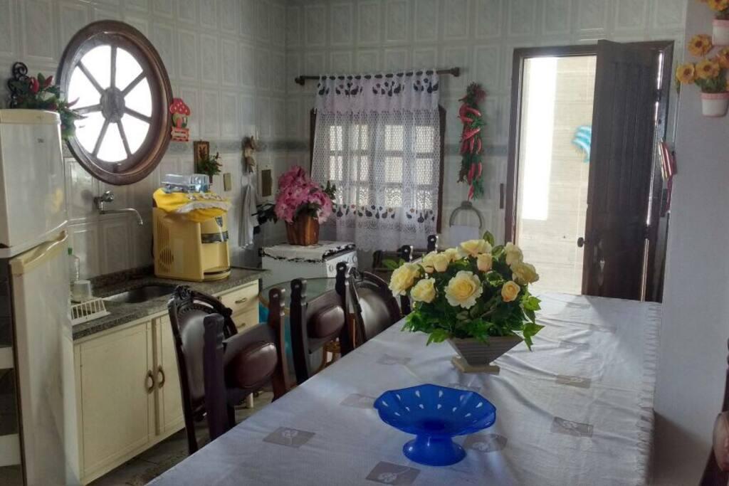 Cozinha equipada com geladeira, fogão, bebedouro e mesa de jantar.