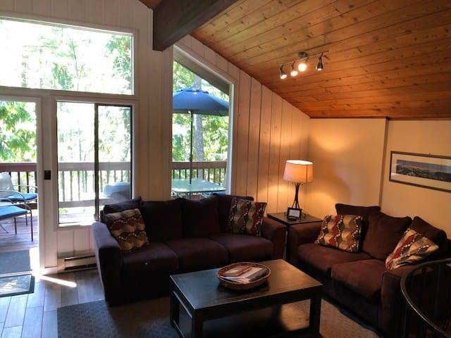 Warm and inviting living area with comfortable couches, LCD tv and large windows, open vaulted ceiling.