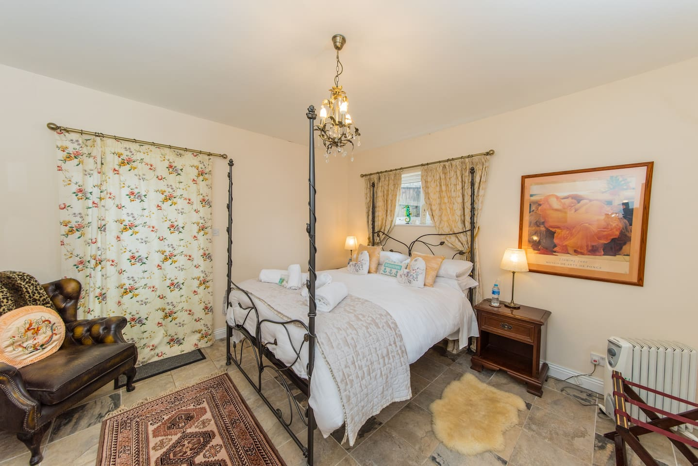 A spacious bedroom leading to the rear decked terrace and garden