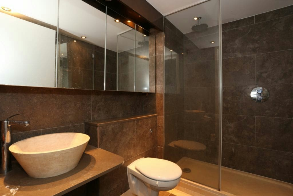 Stone spa bathroom with blue skirting board mood lighting