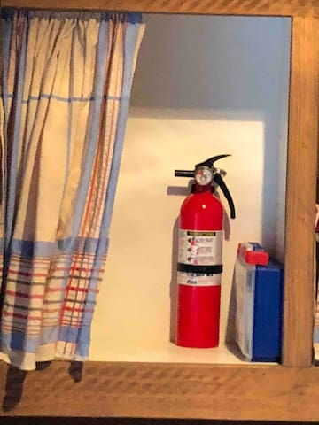 Guest pantry cupboard in solarium kitchenette with first aid kit & fire extinguisher for your safety.