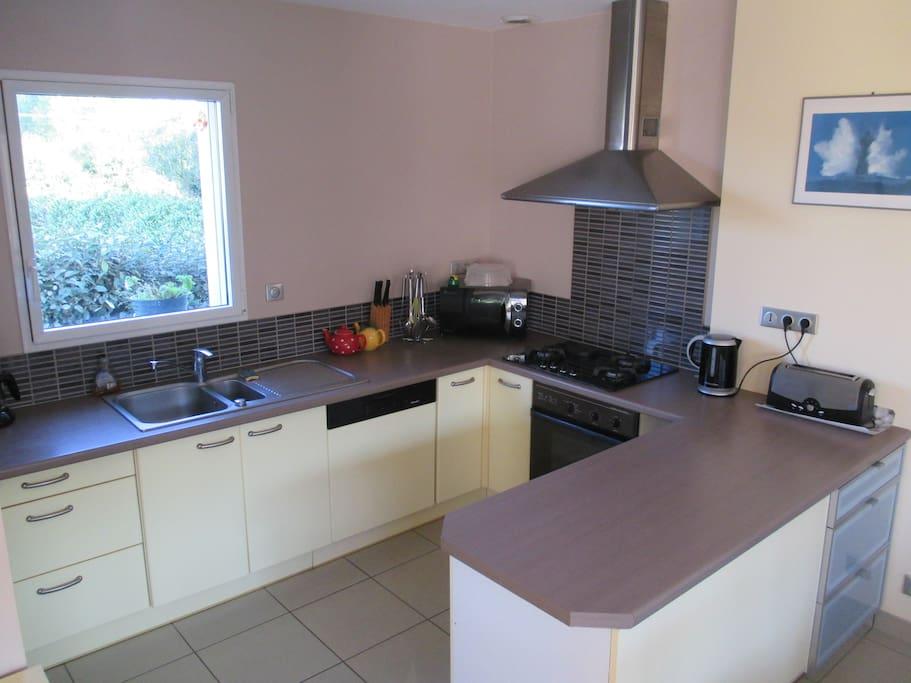 la cuisine ouverte sur le coin repas est bien équipée en vaisselle et ustensiles de cuisine
