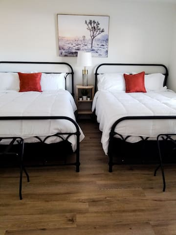 Two queen beds with luggage racks behind modern barn doors