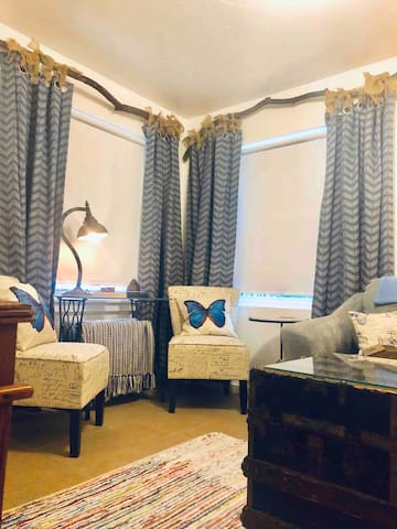 """Here's our cozy living room that features an end table with a phone charging station, desk, 43"""" smart tv, and even an essential oil diffuser with oils! Curtains chairs, couch & pillows are sprayed with Clorox brand sanitizer for colorfast fabrics."""