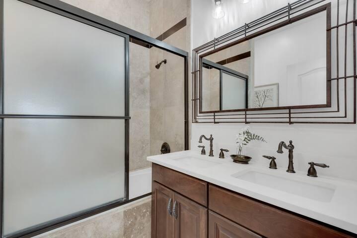Second floor hall bath with double quartz vanity and travertine shower/tub.