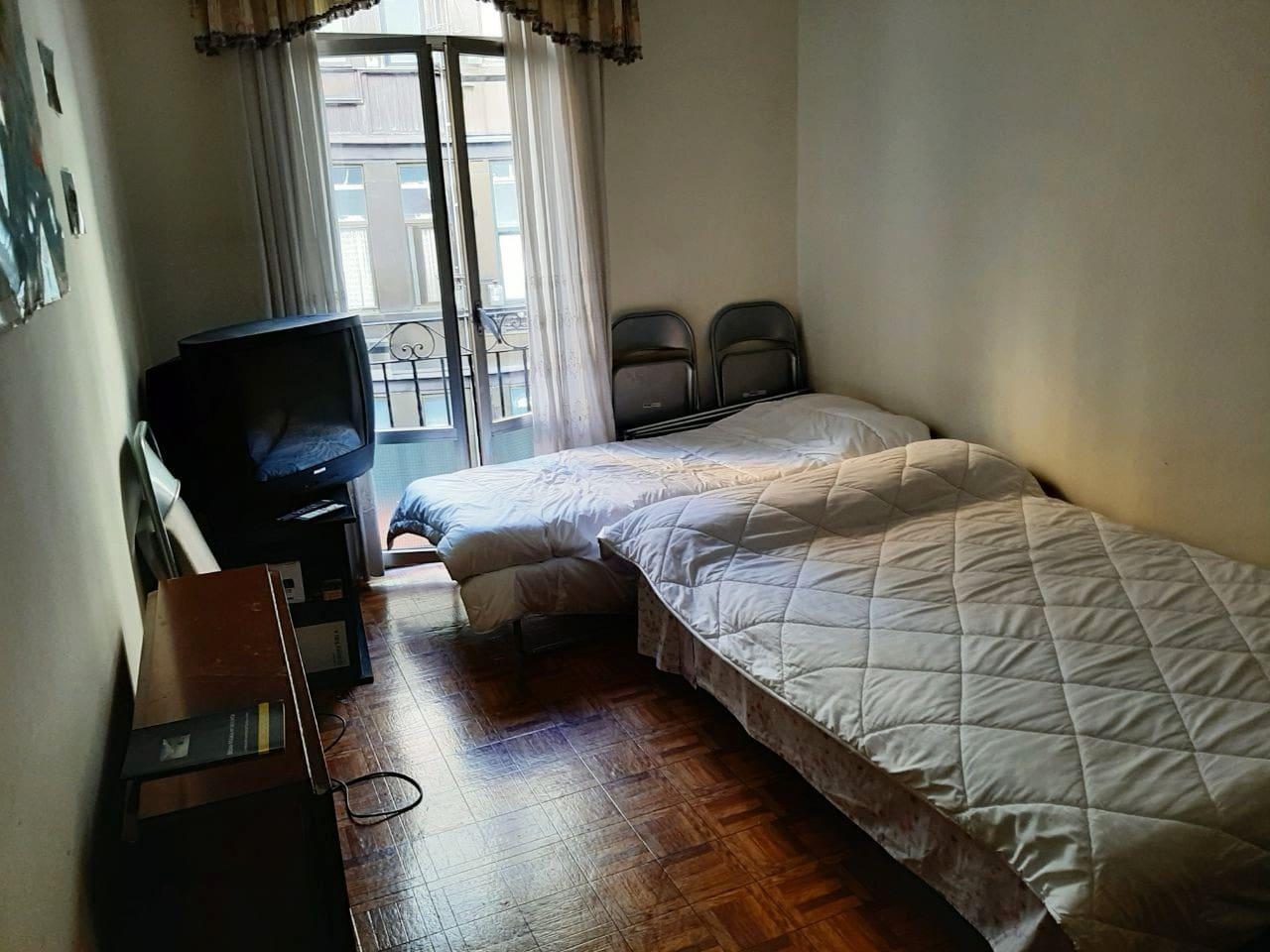 Habitación con amplio sofá cama y cama supletoria individual