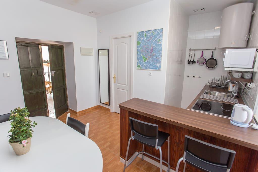 Detalle de la cocina, puerta de entrada, americana y puerta de acceso al cuarto de baño