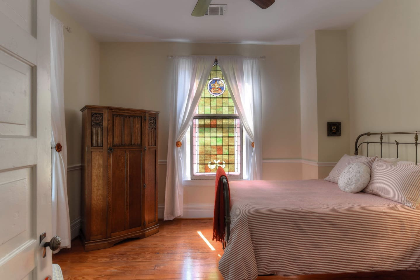 Learning Lamp Room is gilded with the light of an antique stained glass window. Spa robes stored in armoire.