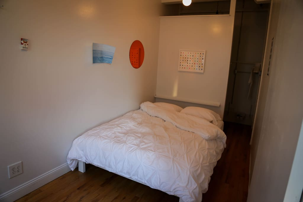 The bedroom is a large separate space with a queen size bed and walk-in closet.