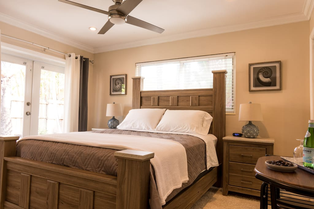Queen sized bed with cafe table & french doors to the pool