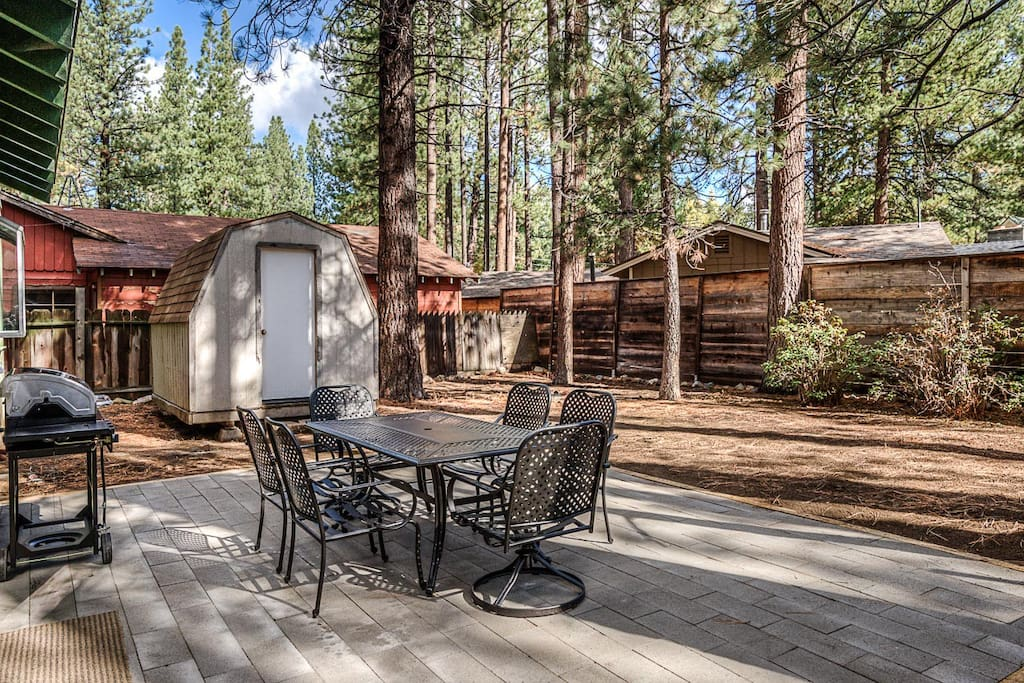 A secluded outdoor patio is shaded by pines.