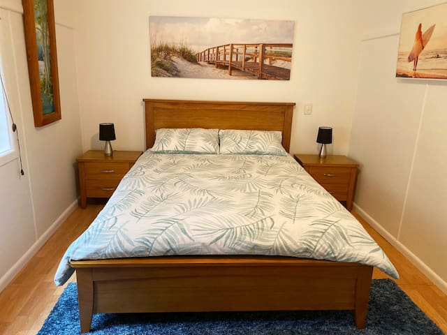 Modern, luxurious queen size bed, roomy bedside tables, and convenient touch lights.