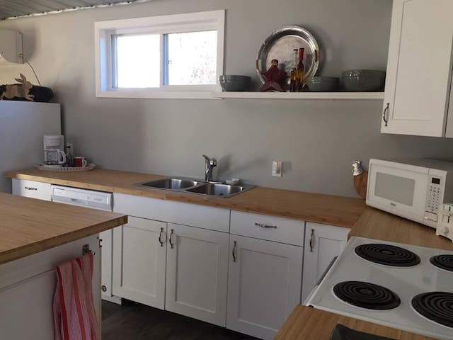 Fully equipped kitchen with fridge, stove, dishwasher, microwave, drip coffee maker and a Keurig, kettle, toaster, dishes, mugs, bowls, glasses, cutlery, pots, pans, cooking utensils...