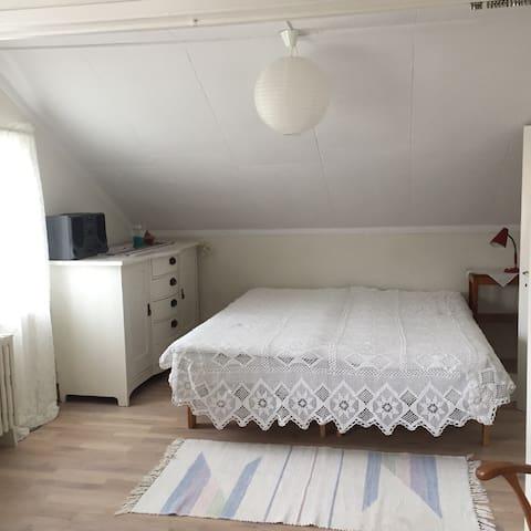 Sovrum med dubbelsäng (del av vardagsrum)