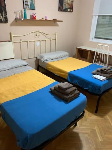 Dormitorio con las dos camas preparadas para dos personas. Una de las camas es la que se pueden doblar las patas y meter debajo de la principal