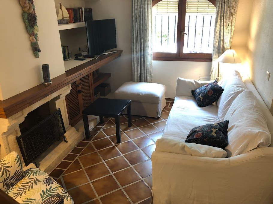 Zona del salón con la chimena, el gran sofa con chaise longue y el sofa orejero con reposapies.