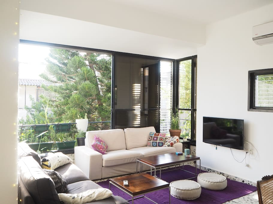 The living room is full with natural sunlight and green view